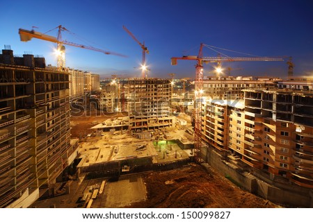 Lots of tower cranes build large residential buildings at night. #150099827