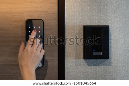 Closeup of a woman's finger entering password code on the smart digital touch screen keypad entry door lock in front of the room. Self Check-in, Airbnb, Modern security, Keyless, Temporary codes. #1501045664