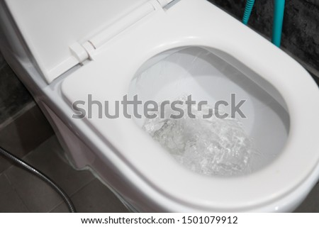 Water flushing in toilet bowl. White hanging toilet seat on white toilet in the home bathroom with grey tiles in concrete style. Bathroom luxury interior. #1501079912
