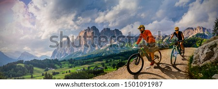 Couple cycling on electric bike, rides mountain trail. Woman and Man riding on bikes in Dolomites mountains landscape. Cycling e-mtb enduro trail track. Outdoor sport activity. #1501091987