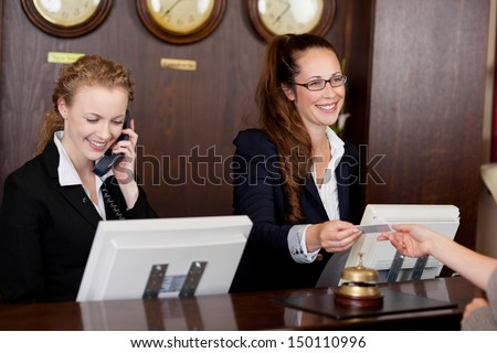 Two beautiful young stylish receptionists at a reception desk, one talking on the telephone and the other handing a card to a customer #150110996