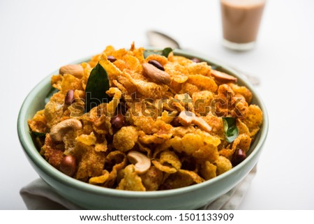 Cornflake Chivda or Corn Chiwda loaded with peanuts and Cashew. Served in a bowl. selective focus #1501133909