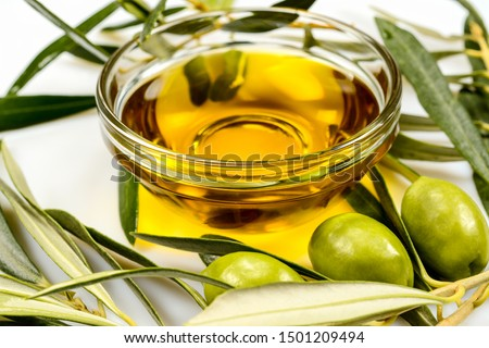 Olive oil. Greek olive oil in glass transparent bowl with olive branches with leaves and olives. Close up on white surface. #1501209494