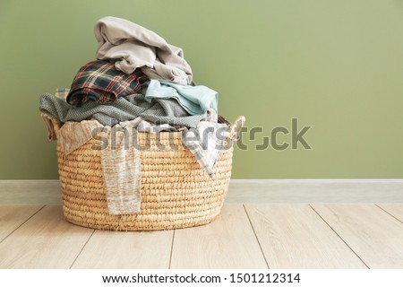 Basket with dirty laundry on floor Royalty-Free Stock Photo #1501212314