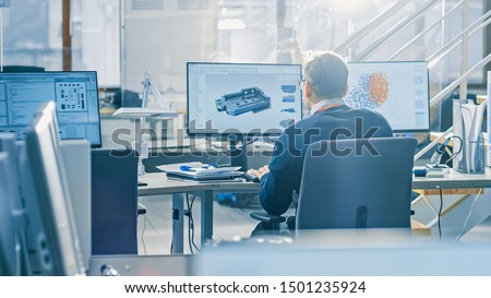 Back View of Industrial Engineer Working on Desktop Computer in Bright Office. Screens Show IDE / CAD Software, Implementation of Machine Learning, Neural Networking and Cloud Computing #1501235924