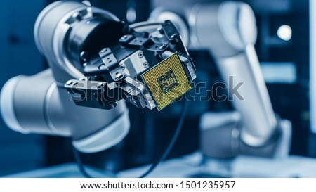 Modern High Tech Authentic Robot Arm Holding Contemporary Super Computer Processor. Industrial Robotic Manipulator End Effector Holding CPU Chip Royalty-Free Stock Photo #1501235957
