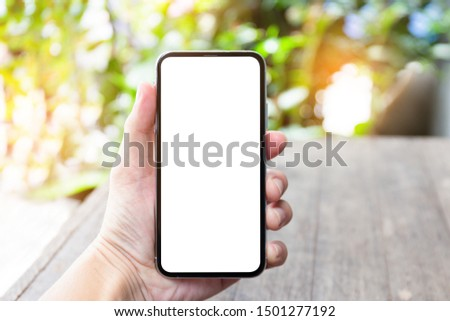 Mockup image blank white screen cell phone.men hand holding texting using mobile on desk at coffee cafe. background empty space for advertise text. contact business,people communication,technology  #1501277192