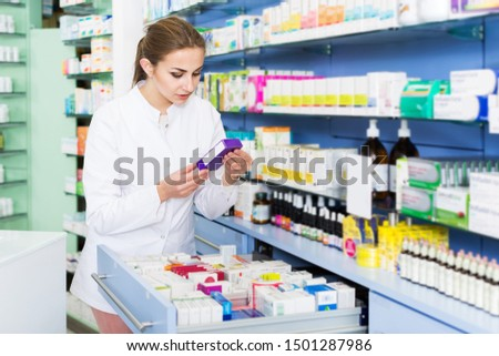 Woman specialist is attentively looking medicines in lockers in drugstore #1501287986
