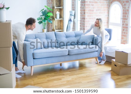 Young beautiful couple moving sofa at new home around cardboard boxes #1501359590
