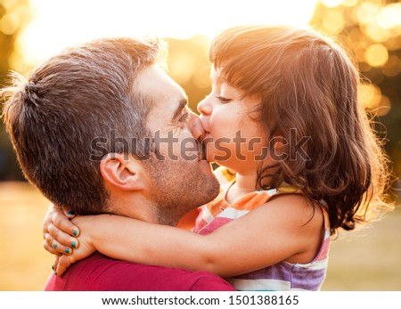 Portrait of father holding daughter in his hands and hugging each other outdoors, little girl kisses him on the nose.