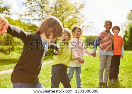 Group of kids holds on to hands in kindergarten or summer camp #1501388888