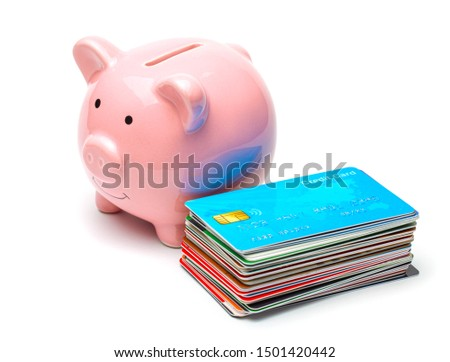 Pink piggy bank and credit cards in a stack isolated on white background. How to save money on a credit card #1501420442