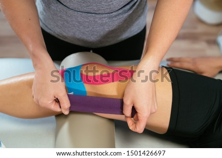 Photo detail of the hands of a physiotherapist woman gluing purple medical tape on another celestial tape and another pink one on the knee of a patient. Concept of muscle health and relaxation. #1501426697