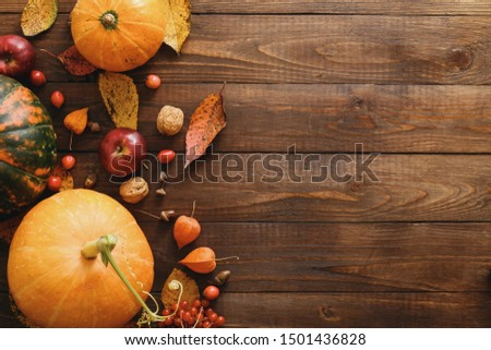 Autumn composition. Pumpkins, fallen leaves, apples, red berries, walnuts on wooden table. Happy Thanksgiving concept. Flat lay, top view, copy space #1501436828