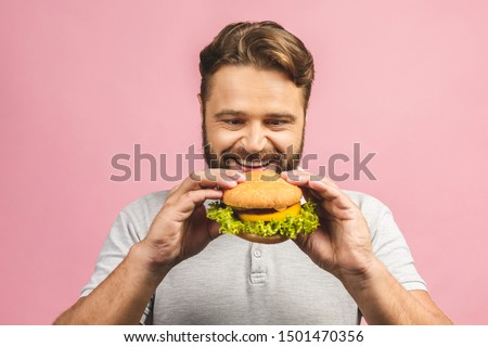 Young man holding a piece of hamburger. Bearded gyu eats fast food. Burger is not helpful food. Very hungry guy. Diet concept. Isolated over pink background. #1501470356