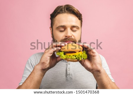 Young man holding a piece of hamburger. Bearded gyu eats fast food. Burger is not helpful food. Very hungry guy. Diet concept. Isolated over pink background. #1501470368