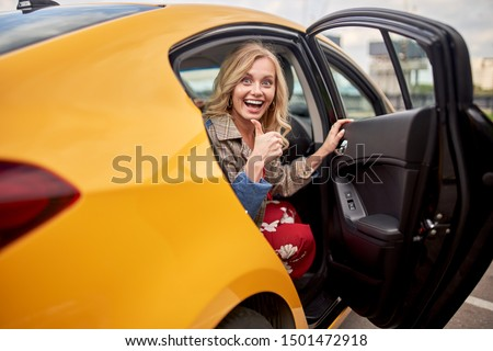 Photo of enthusiastic blonde sitting in back seat of yellow taxi with door open #1501472918