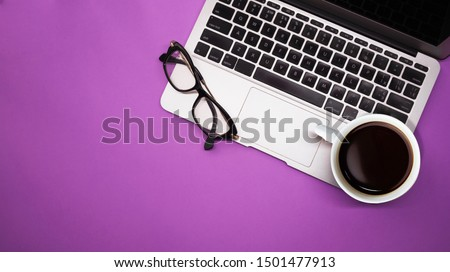 gray laptop with a cup of coffee and glasses on purple background table, working place at home or in the office Royalty-Free Stock Photo #1501477913