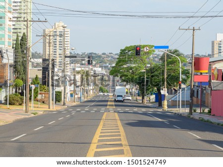 Large avenue with four lanes, few cars on the street, local commerce and buildings around. Photo on the middle of the avenue. Ceara avenue at Campo Grande MS, Brazil. Royalty-Free Stock Photo #1501524749