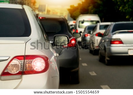Luxury of white car stop on the asphalt road. Traveling in the provinces during on evening. Open light brake. With tree and city. Traffic jam after to work in an urban area. #1501554659