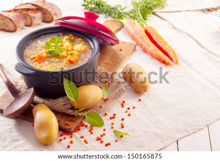 Delicious thick vegetable stew or soup in a pot surrounded by scattered fresh vegetables and ingredients in a rustic kitchen