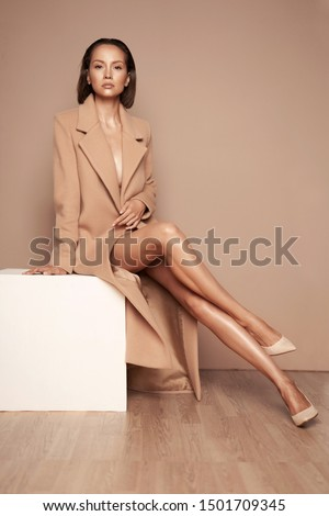 Fashion studio photo of young beautiful lady in beige coat on beige background. Total beige. Fashion look book. Warm Autumn. Warm Spring #1501709345