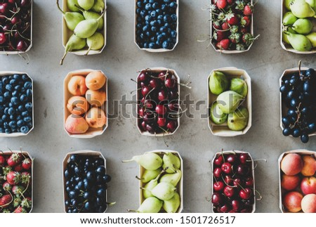 Summer fruit, berry assortment. Flat-lay of fresh strawberries, cherries, grape, blueberries, pears, apricots, figs in eco-friendly boxes over grey background, top view. Local farmers market produce #1501726517