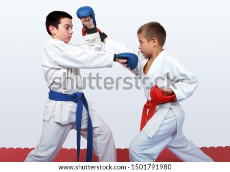 With a red and a blue belt athletes doing paired exercises  karate #1501791980