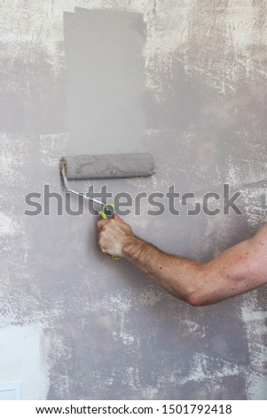 Close up of painter hand in white glove painting a wall with paint roller; copy space #1501792418