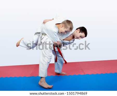 Boy athlete with a red sash makes hip throw #1501794869