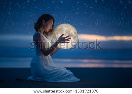 Delicate photography, Astrology, Women's magic. Beautiful attractive girl on a night beach with sand and stars hugs the moon, art photography. #1501921370