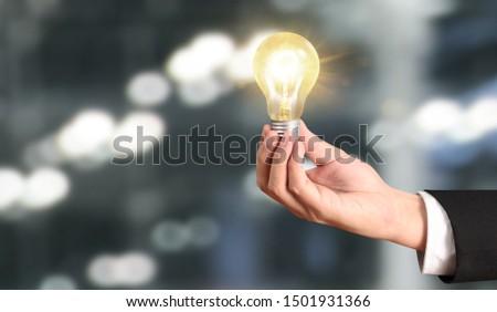 Hand of holding illuminated light bulb, idea, innovation inspiration concept #1501931366