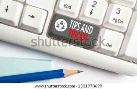Handwriting text writing Tips And Tricks. Concept meaning means piece advice maybe suggestion how improve White pc keyboard with empty note paper above white background key copy space.