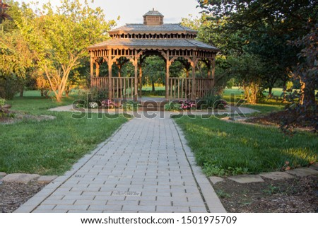 Gazebo in park setting with brick pathway leading up to the front. flowers planted around the outside. #1501975709