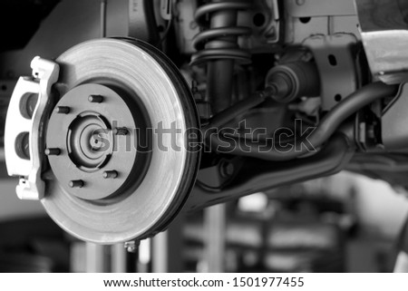 Disc brake of the vehicle for repair, in process of new tire replacement. Car brake repairing in garage.Suspension of car for maintenance brakes and shock absorber systems.Close up.         Royalty-Free Stock Photo #1501977455