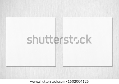 Two empty white square flyer or business card mockups with soft shadows on neutral light grey textured background. Flat lay, top view