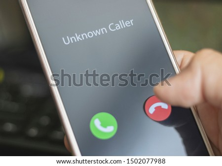 Unknown caller. A man holds a phone in his hand and thinks to end the call. Incoming from an unknown number. Incognito or anonymous #1502077988