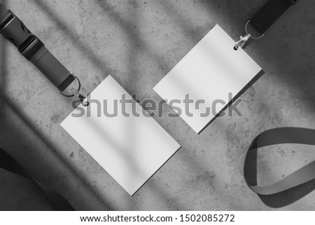 Two blank white ID security cards with a dark ribbon on a concrete gray table. Mock up. 3d rendering