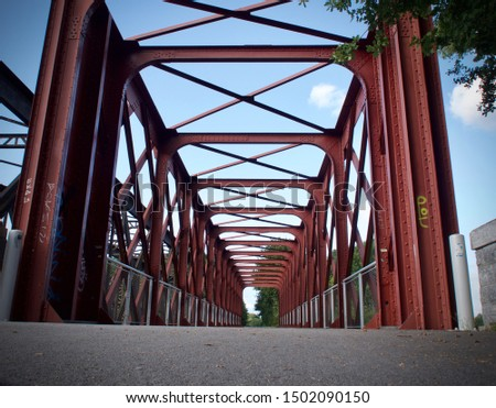 road under the steel structure of an old metal bridge. City life, urban scene, light car routes, transport and traffic concept. Picture from the bottom of the tunnel perspective