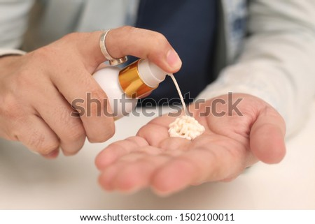 Picture of man spray medicine bottle holding in hand. Isolated on white background. #1502100011