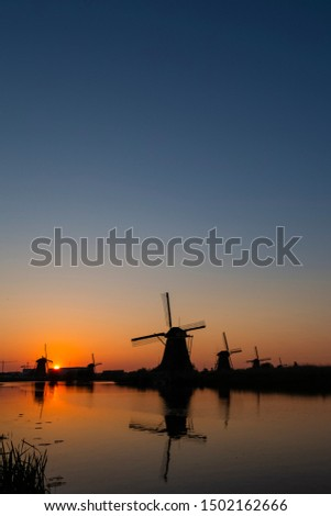 Beautiful Romantic Dutch Windmills in Front of The River in Kinderdijk Village in the Netherlands. Picture Taken At Golden Hour. Vertical Shot