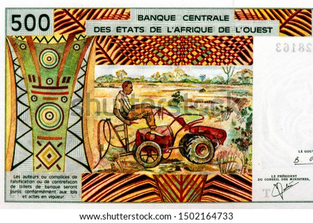 """Picture of a farmer and a tractor. Portrait from African States, 500 Francs 1961 banknote. The letter """"T"""" in Togo, African States money. Close Up UNC Uncirculated - Collection."""