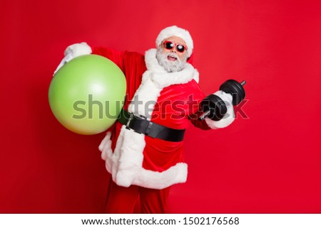 Portrait of excited christmas father in eyewear eyeglasses practice fitness with dumbbells fitball isolated over red background #1502176568