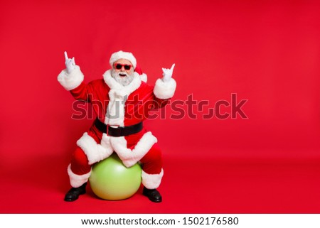 Full length body size view of his he nice attractive cheerful cheery glad fat bearded Santa working out sitting on pilates ball showing horn sign heavy metal isolated over bright vivid red background #1502176580