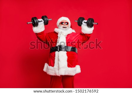 Portrait of his he nice attractive cheerful cheery glad positive fat overweighed bearded Santa working out barbell physical exercise isolated over bright vivid shine red background #1502176592