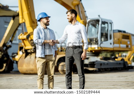 Builder choosing heavy machinery for construction, talking with a sales consultant on the open ground of a shop with special vehicles Royalty-Free Stock Photo #1502189444