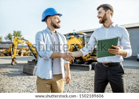 Builder choosing heavy machinery for construction with a sales consultant shaking hands on the open ground of a shop with special vehicles #1502189606