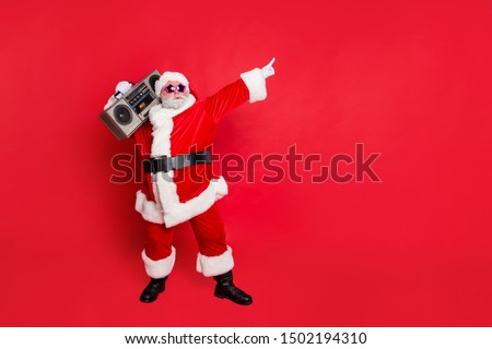 Full body photo of funny cute santa claus with sound boom disco box dancing wearing style eyeglasses eyewear headwear hat isolated over red background #1502194310