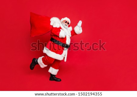 Full length body size view of cheerful cheery dreamy glad funky fat overweight plump gray-haired bearded man piggy backing gifts fairy waving greetings isolated over bright vivid shine red background #1502194355