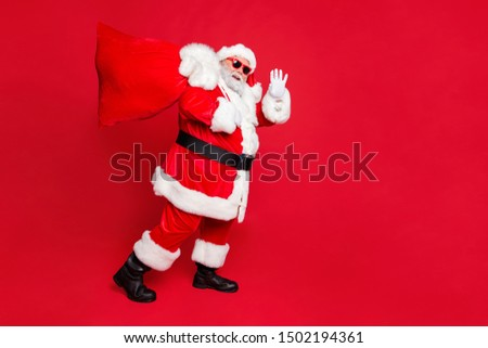 Full length body size view of cheerful cheery funky fat overweight plump gray-haired bearded man piggy backing gifts winter tradition waving greetings isolated over bright vivid shine red background #1502194361